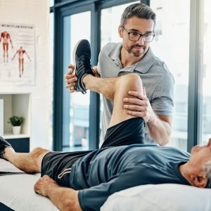 A health practioner stretches a patient's leg on a bed.