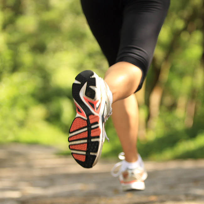 Fit person runs on outdoor trail.