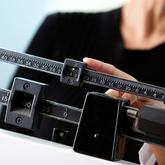 Health professional weighs person on scale.