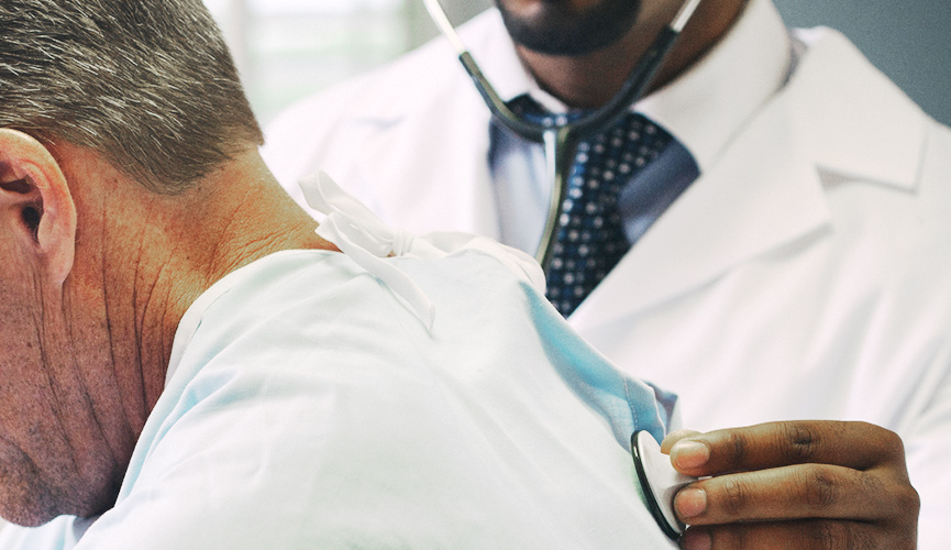 Physician uses a stethoscope to listen to a patient's heartbeat.