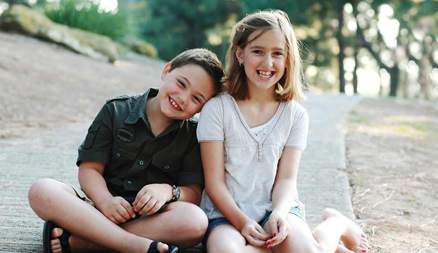 Two smiling children sit together outdoors on the pavement.