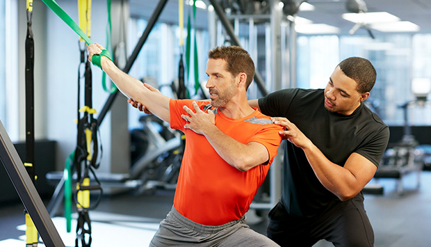 A fit man uses a green stretching band in a gym to stretch his arm away from the band, as a personal trainer gently guides his shoulder and arm in the same direction.