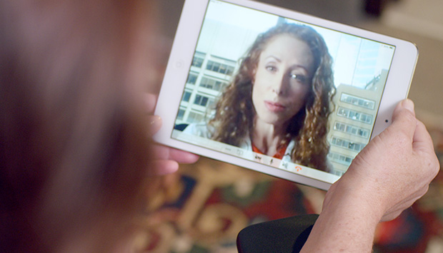 Person has virtual call with medical professional on a tablet.