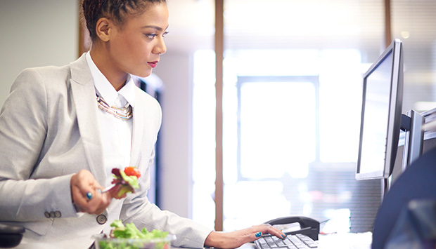 Business woman eats a healthy meal while working