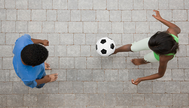 Child kicks soccer ball to another child as they wait to receive it.