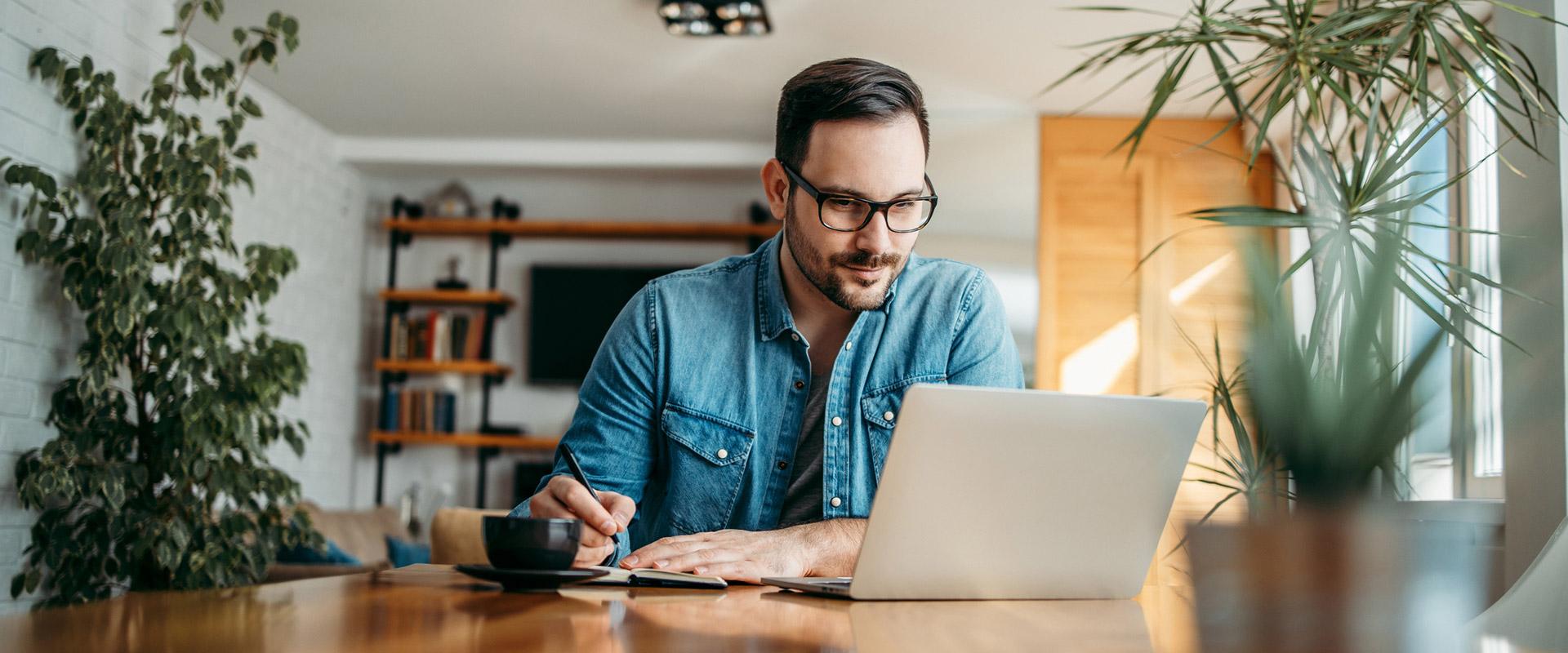 man on laptop taking notes